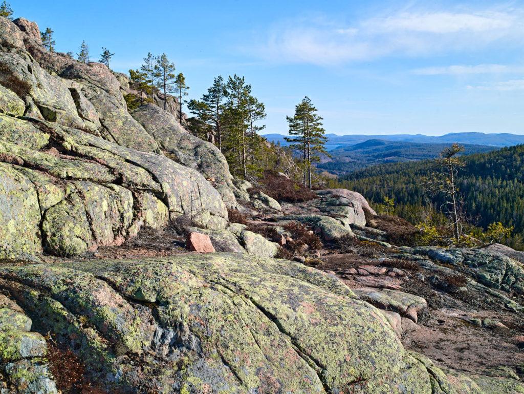 Vy över röd nordingrågranit och frodiga granskogar från Slåttdalsberget